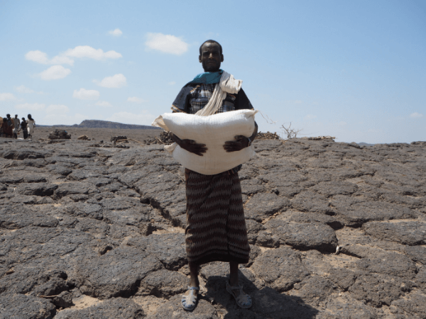 Afar man holds 50kg sack of wheat