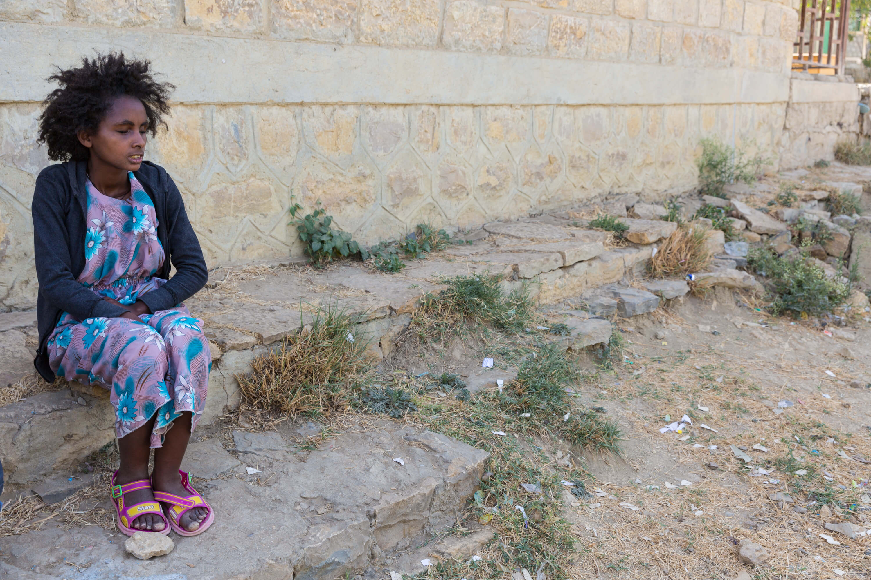 Ethiopian woman sitting alone outside on stoop